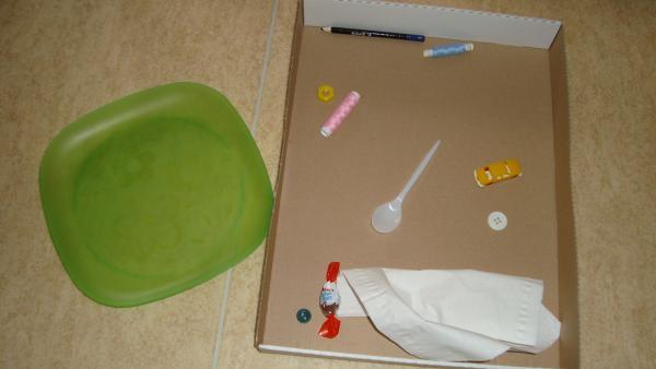 Die Materialien für das Spiel: Ein Karton mit verschiedenen Gegenständen (z.B. Spielzeug, Stiften, Taschentüchern) und ein  grüner Plastikteller. | Rechte: KiKA