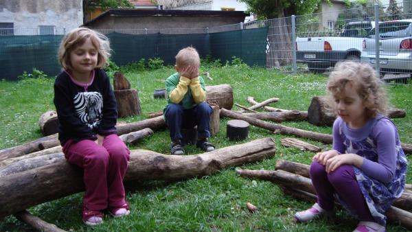 Kinder sitzen mit geschlossenen Augen im Garten. | Rechte: KiKA