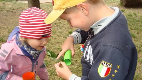 Junge und Mädchen schauen auf ein Blatt. | Rechte: KiKA