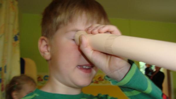Kind schaut durch ein zusammengerolltes Stück Papier | Rechte: KiKA