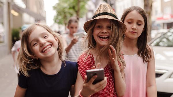 Drei Mädchen laufen lachend eine Straße entlang. Eine von ihnen hat ein Smartphone in der Hand. | Rechte: KiKA