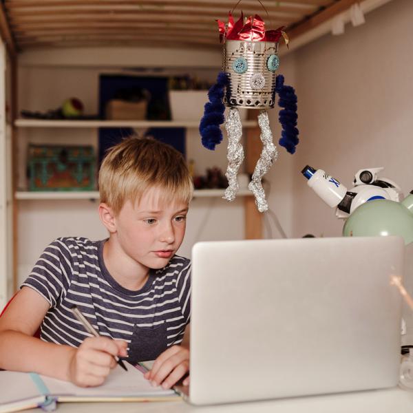 Ein Junge sitzt am Schreibtisch und arbeitet mit einem Laptop. | Rechte: KiKA