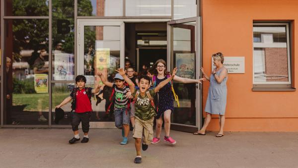 Die Kinder freuen sich auf die Pausenzeit und stürmen aus dem Schulgebäude. | Rechte: KiKA/Mira Mikosch