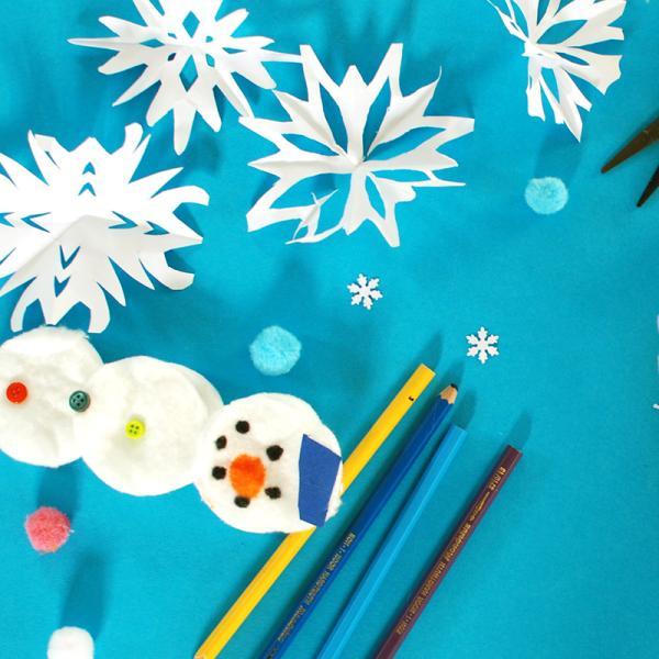 Bastelideen für den Winter. Ein blauer Untergrund mit Bastelmaterialien, wie Schere, Stften und Kleber. Darauf sind Schneeflocken aus Papier, ein Schneemann aus Wattepads und ein Eisstänbchenspiel aus der Sesamstraße.  | Rechte: KiKA