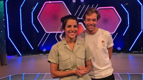 Clarissa Corrêa da Silva und Tobias Krell stehen in einem Studio und lächeln in die Kamera.   Rechte: KiKA
