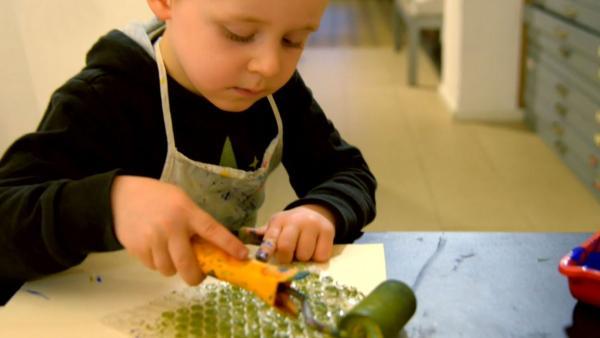 Kind bemalt Luftpolsterfolie mit Farbe. | Rechte: KiKA