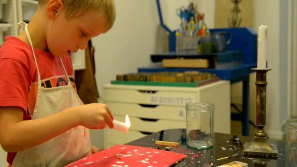 Junge kleckert Wachstropfen einer Kerze auf ein Blatt | Rechte: KiKA