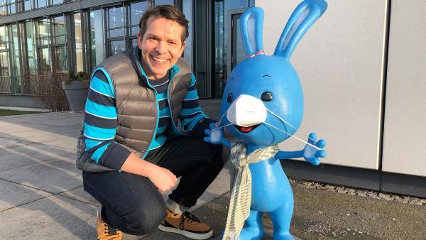 Moderator Juri hockt neben einer Kikaninchen-Figur. Die Figur ist ein Hase und trägt eine Maske und einen Schal. | Rechte: KiKA/ Alina Höngen