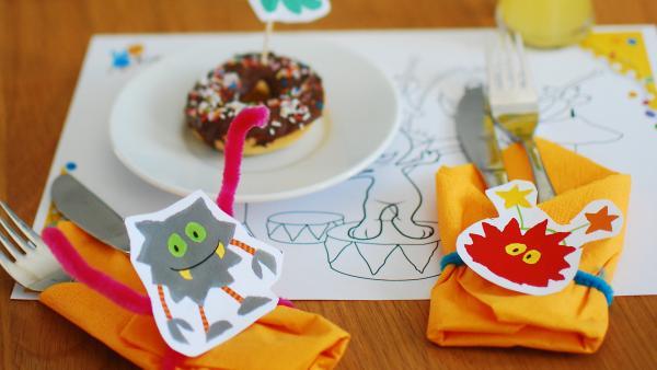 Partytisch mit Besteck, welches dekorativ mit Monsterstrickern angerichtet ist. Dahinter ist ein teller auf dem ein Muffin ist.  | Rechte: Franziska Spanger / KiKA