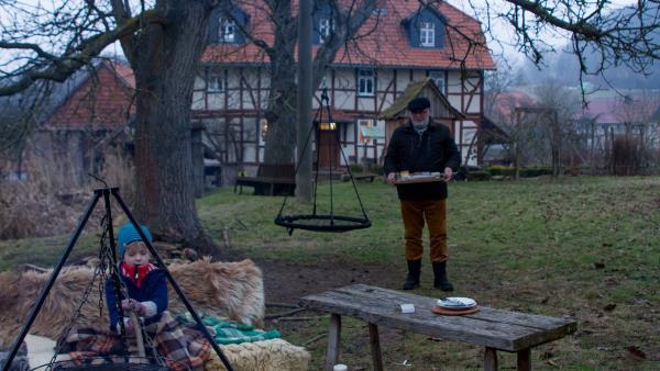 Opa Karl (Peter Rauch) kommt mit dem Fisch an das Lagerfeuer. | Rechte: KiKA/Kinderfilm GmbH 2017