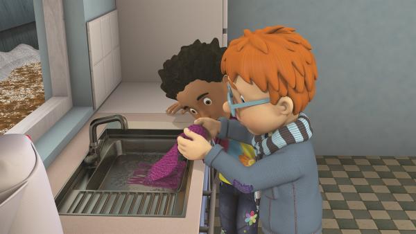 Norman versucht, den Schmutz aus dem Schal zu waschen. | Rechte: KiKA/2011 Prism Art & Design Limited
