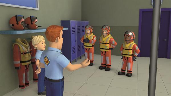 Die Feuerwehrleute trainieren, so schnell wie möglich ihre Anzüge für Rettungseinsätze anzuziehen. Sam stoppt die Zeit.  | Rechte: KiKA/Prism Art & Design Limited