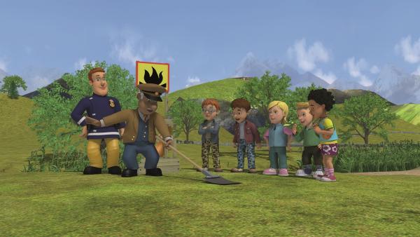 Sam erklärt den Pfadfindern, wie sie ein kleines Feuer löschen können. Trevor probiert eine Feuerpatsche aus.    Rechte: KiKA/Prism Art & Design Limited