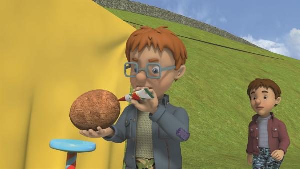 Norman trickst an seiner Wurfbude und klebt die Kokosnüsse fest.   Rechte: KiKA/Prism Art & Design Limited