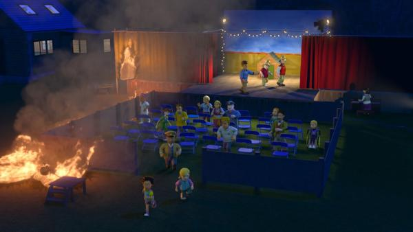Während der Vorstellung löst ein umgefallener Scheinwerfer einen verehrenden Brand aus. Die Zuschauer bringen sich in Sicherheit. | Rechte: KiKA/Prism Art & Design Limited