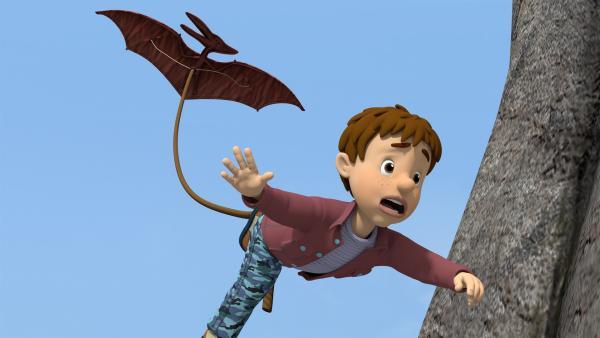 Norman hat seinem Cousin Derek einen Streich gespielt. Dass Derek an einem Pterodactylus-Drachen davonfliegt, hat er aber nicht geplant. | Rechte: KiKA/Prism Art & Design Limited