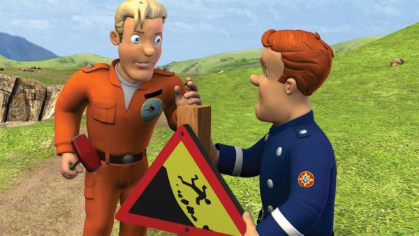 Feuerwehrmann Sam und Tom Thomas stellen Warnschilder auf. Die Wege entlang der Klippen sind brüchig. | Rechte: KiKA/HIT Entertainment