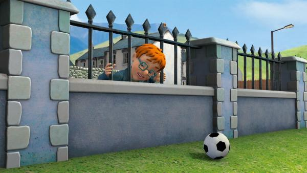 Beim Versuch seinen Fußball wiederzubekommen bleibt Norman mit dem Kopf zwischen den Gitterstäben klemmen. | Rechte: KiKA/HIT Entertainment