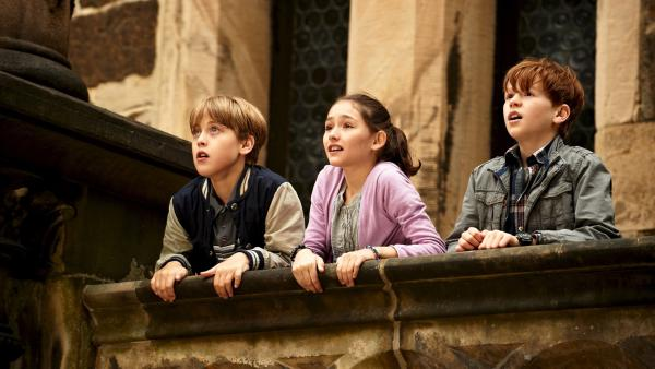 Karl (Jonas Holdenrieder, re.), Marie (Emily Kusche) und Hannes (Nico Hartung) beobachten mit Spannung vom Burgbalkon aus, was draußen vor sich geht. | Rechte: ZDF/Universum Film