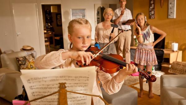 Vilja (Sirkku Ullgren) beim Geigespielen mit ihrer Mutter Anna (Merja Pennanen), ihrem Vater Jouni (Pekka Strang) und der lästigen großen Schwester Vanamo (Kiia Kokko) | Rechte: KiKA/KEVIN LEE Film GmbH