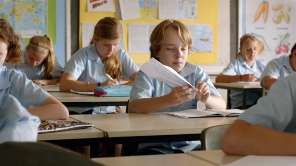Dylan (Ed Oxenbould) baut einen Papierflieger in der Schule. | Rechte: MDR/Arenamedia Melbourne