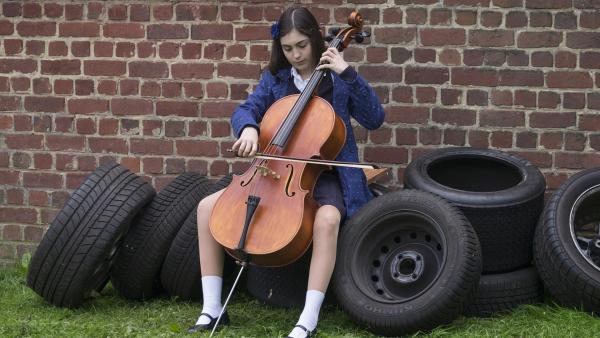 Marie (Alix Vaillot) übt Cello vor der Garage von Victors Vater.   Rechte: MDR/Ajoz Films/Gaumont/France 2 Cinema/Les Magnifiques/Nexus Factory