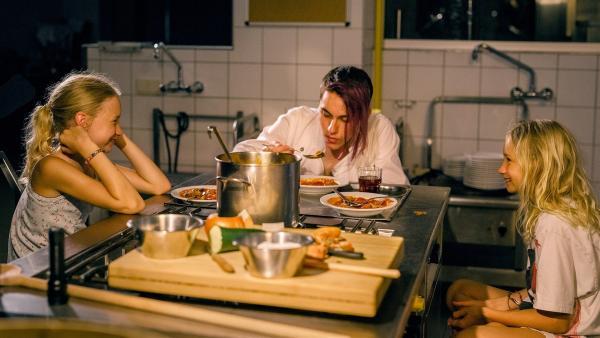 Lotte (Delphine Lohmann, links) bringt ihrer Schwester Luise (Mia Lohmann) Kochgerichte bei. Koch Matteo (Vincent Sauer) hilft ihnen dabei. | Rechte: SWR/Uschi Reich