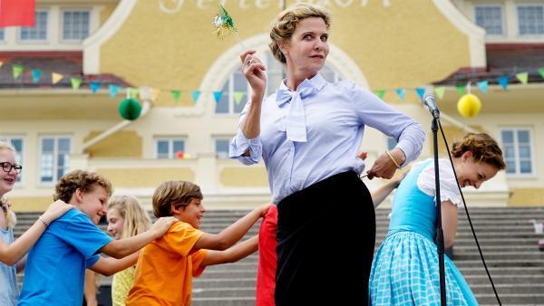 Frau Muthesius (Margarita Broich) feiert mit den Kindern das Abschiedsfest vom Sommercamp. | Rechte: SWR/Uschi Reich