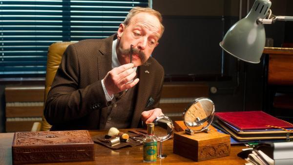 Schuldirektor Schnauzer (Harry Piekema) lässt sich nur ungern bei der Pflege seines Schnauzbartes stören. | Rechte: ZDF/PVPictures by Jaap Vrenegoor
