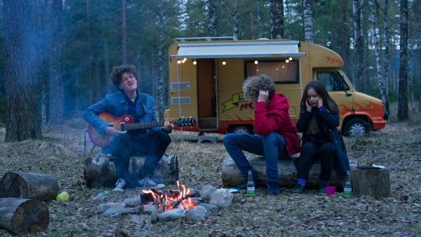 Axel (Jakob Dyrud) spielt am Lagerfeuer einen schrägen Song. | Rechte: NDR/Bjorn Bratberg