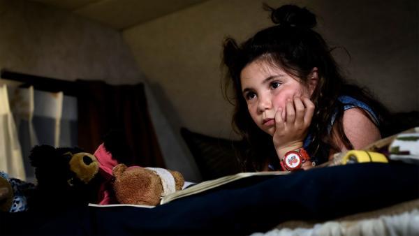 Jip (Layla Zara Seme) schreibt in ihrem Bären-Expeditionsbuch, während sie ihre Familie betrachtet. | Rechte: NDR/Pief Weyman