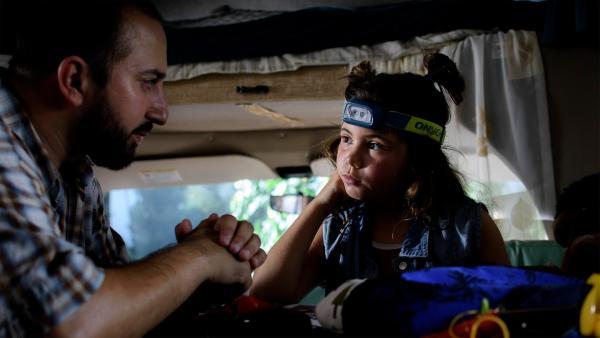Papa (Gürkan Küçüksentürk) entschuldigt sich bei Jip (Layla Zara Seme) für die Verzögerung ihrer Reise in den Nationalpark. | Rechte: NDR/Pief Weyman