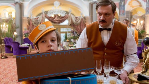 Timm (Arved Friese, l.) darf im Grand Hotel als Liftboy arbeiten und lernt dort den Kellner Kreschimir (Charly Hübner, r.) kennen. | Rechte: ZDF/Gordon Muehle