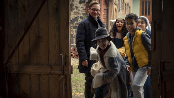 Der Pfarrer (Arndt Schwering-Sohnrey, l.) bietet den Kindern die Scheune für ihr Krippenspiel an. (Paul (Sanusi Bah, v.r.), Sidra (Hannie Boon, h.r.), Sophie (Luiza Dandara Guimaraes, M.)) | Rechte: KiKA/MDR/TELLUX film/CROSS MEDIA/Conny Klein