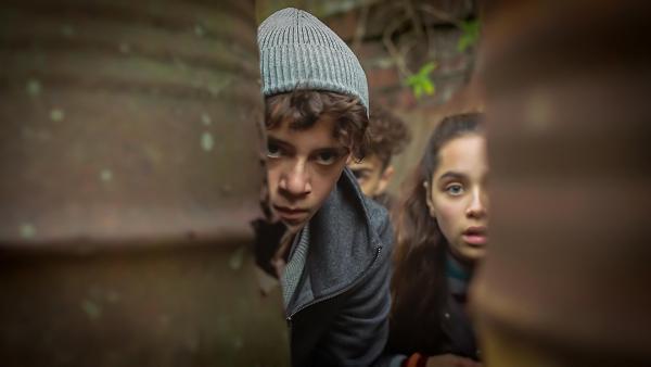 Auf der Suche nach Beweisen schleichen Paul (Sem Hulsmann), Sara (Faye Kimmijser) und Kai (Narek Awanesyan) an Soldaten vorbei. | Rechte: NDR/Umami Media