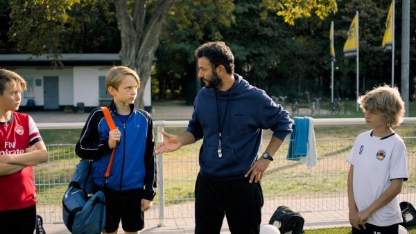 Trainer Rainer (Mohamed Achour) stellt Ben (Yoran Leicher) der Mannschaft des SC Düren vor. | Rechte: NDR/Weydemann Bros.GmbH/Monika Plura