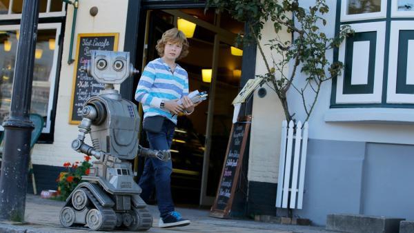 Tobbi (Arsseni Bultmann) zeigt seinem neuen Freund, Roboter Robbi, seinen Heimatort Tütermoor. | Rechte: ZDF/Tom Trambow