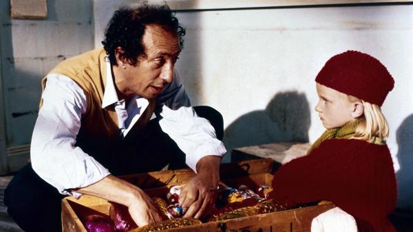 Weil er seinen Süßwarenladen aufgibt, schenkt Vasilis (Renzo Spinetti) Lotta (Grete Havneskjøld) eine große Kiste mit Schokolade. | Rechte: ZDF/Jan Rydqwist