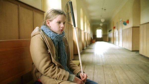 Marie (Ricarda Ramünke) wartet vor dem Musiksaal auf ihre Freundin Inga, um ihr große Neuigkeiten zu berichten.   Rechte: Joseph Wolfsberg