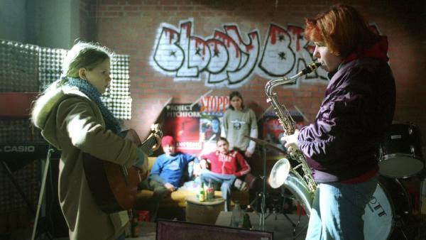 Marie (Ricarda Ramünke, li.) und Inga (Marie Rother, re.) demonstrieren vor einer Band ihre musikalischen Fähigkeiten.   Rechte: Joseph Wolfsberg