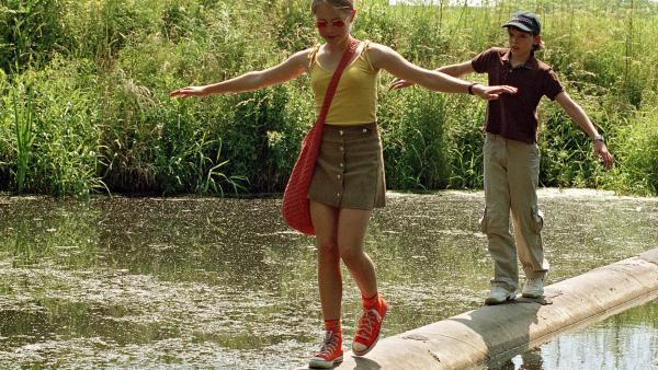 Silke (Lea Eisleb) und Martin (Johann Hillmann) laufen auf ihrem Weg zum Riverpool über eine alte Mauer.  | Rechte: RBB/Joseph Wolfsberg