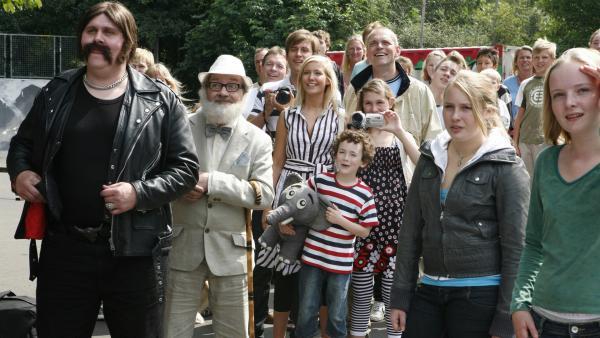 Pa und seine Kinder Søs (gestreiftes Kleid), Mie (mit Videokamera) und Per (mit Elefant Bodil) während Oles Skateboard-Wettbewerb. Onkel Anders (mit Hut) und Søs Freund Peter sind auch dabei. | Rechte: KiKA/Ilse Schoutteten