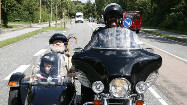 Onkel Anders (Jess Ingerslev, hinten sitzend) und Per (Kasper Kesje) unternehmen eine kleine Motorradtour. | Rechte: KiKA/Ilse Schoutteten
