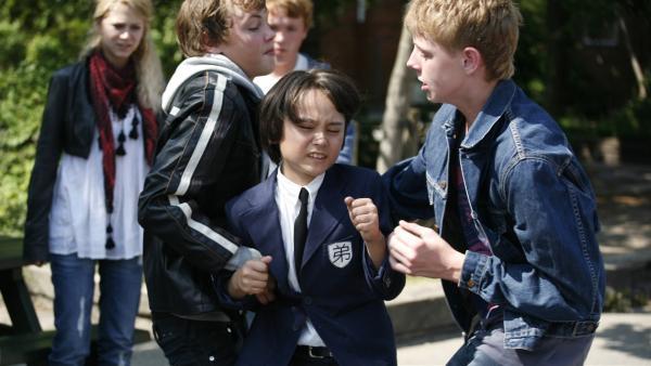 Shin (Miki Andersen) wird von älteren Schülern angegriffen. Doch er weiß sich auf seine Art zu wehren. | Rechte: KiKA/Ilse Schoutteten