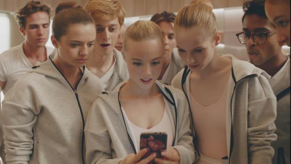 Die Mitschüler von Lena (v.l.n.r.: Kennedy (Caitlin-Rose Lacey), Jeff (Castle Rock Peters), Bree (Chloe Fox), Max (Rory J. Saper), Thea (Hannah Dodd), Dash (Hiran Abeysekera) und Ines (Eubha Akilade) sind neugierig wer Lena ist und woher sie kommt. Im Internet finden sie ein Porträt, das Lena zum verwechseln ähnlich sieht.  | Rechte: ZDF/Cottonwood Media 2018