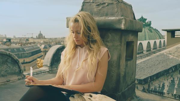 Lena (Jessica Lord) schreibt an ihren Freund Henri. Die große Aufführung im Opernhaus steht bevor und alles sind sehr aufgeregt. | Rechte: ZDF/Cottonwood Media 2018
