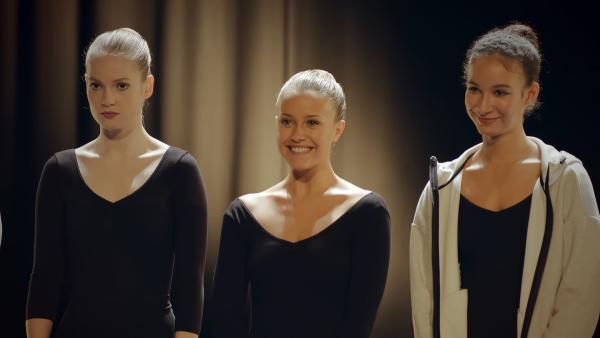 Thea (Hannah Dodd. v.l.) ist sauer. Sie ist nicht zufrieden mit ihrem Auftritt, während Lena (Jessica Lord und Ines (Eubha Akilade) sehr glücklich über ihre gute Präsentation sind. Gespannt warten die drei auf die Beurteilung durch die Schuldirektorin. | Rechte: ZDF/Cottonwood Media 2018