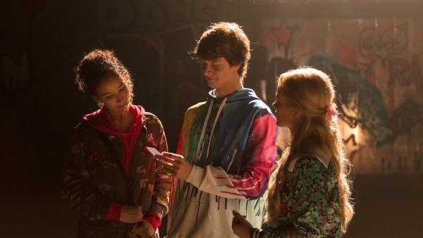 Jeff (Castle Rock Peters, M.) zeigt Ines (Eubha Akilade, l.) und Lena (Jessica Lord, r.) die Einladung von Max. Max möchte mit ihnen weiter heimlich Hip-Hop tanzen. | Rechte: ZDF/Cottonwood Media/Nicolas Velter