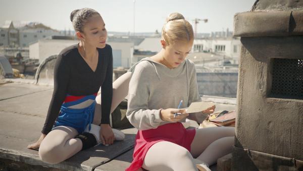 Lena (Jessica Lord, r.) liest Ines (Eubha Akilade, l.) den neuesten Brief von Thea vor, die aus dem Jahr 1905 schreibt. Über den magischen Schornstein auf dem Dach der Oper können sie Nachrichten austauschen. | Rechte: ZDF/Cottonwood Media/Nicolas Velter