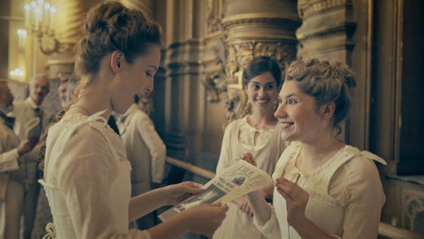 Claudine (Audrey Hall, r.) zeigt Thea (Hannah Dodd. l.) einen Artikel in der Zeitung. Darin wird Thea als neuer Star am Balletthimmel gefeiert. | Rechte: ZDF/Cottonwood Media/Nicolas Velter